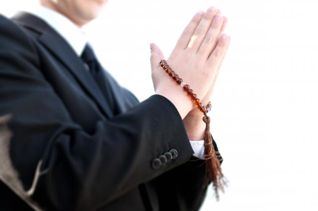 数珠を持って手を合わせる男性